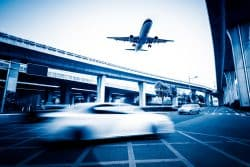 Blurred Street Scene In City With A Plane Flying Over
